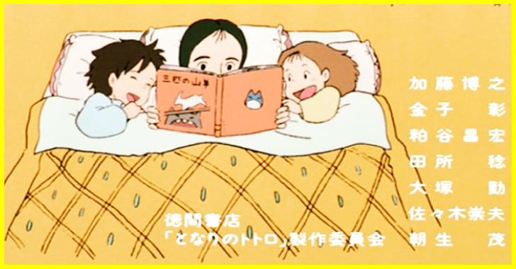 母娘3人で仲良く布団で絵本を読んでいるシーン